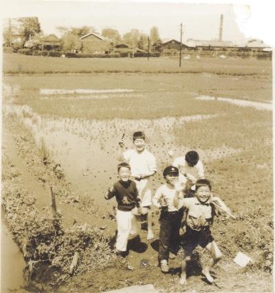 田んぼで遊ぶ子どもたち ‐ 背景に藤野缶詰工場