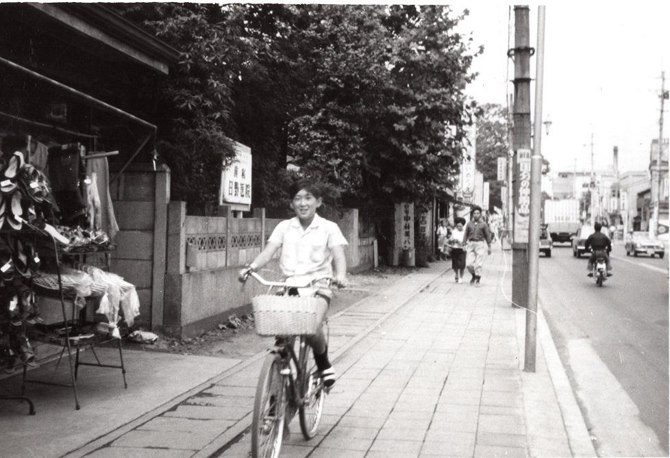 日野歯科医院前を自転車で走る少年